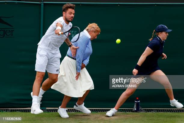Switzerland's Stan Wawrinka collides with the line judge as he chases a return against US player Reilly Opelka during their men's singles second...