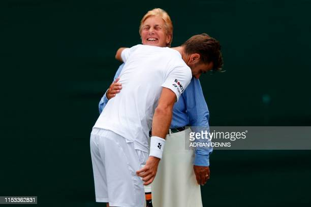Switzerland's Stan Wawrinka gives a line judge a hug after colliding with her going for a return against US player Reilly Opelka during their men's...