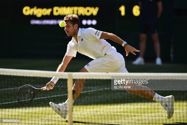 Switzerland's Stan Wawrinka returns to Bulgaria's Grigor Dimitrov during their men's singles first round match on the first day of the 2018 Wimbledon...