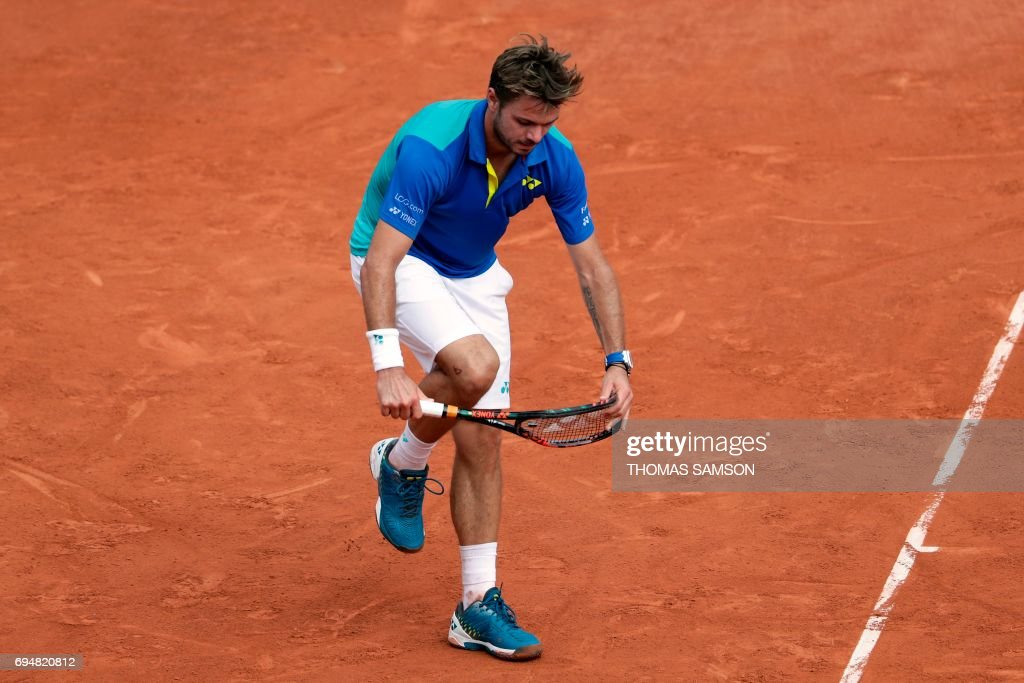TOPSHOT - Switzerland's Stanislas Wawrinka breaks his racket during the men's final tennis match against Spain's Rafael Nadal at the Roland Garros 2017 French Open on June 11, 2017 in Paris. / AFP PHOTO / Thomas SAMSON