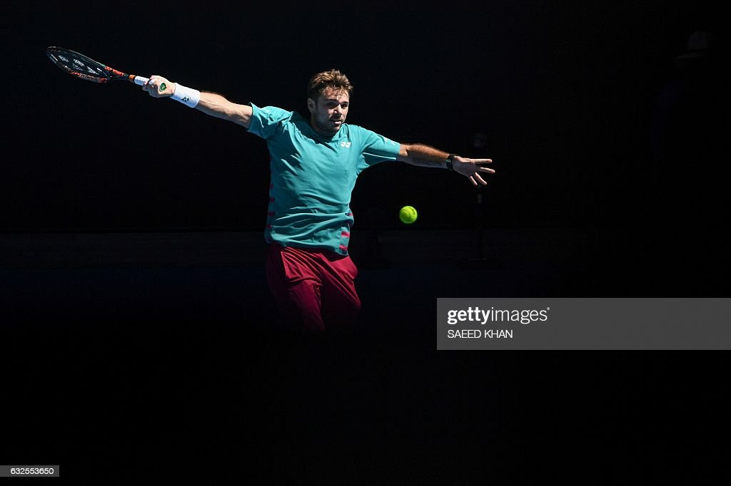 TOPSHOT - Switzerland's Stanislas Wawrinka hits a return against France's Jo-Wilfried Tsonga during their men's singles quarter-final match on day nine of the Australian Open tennis tournament in Melbourne on January 24, 2017. / AFP / SAEED