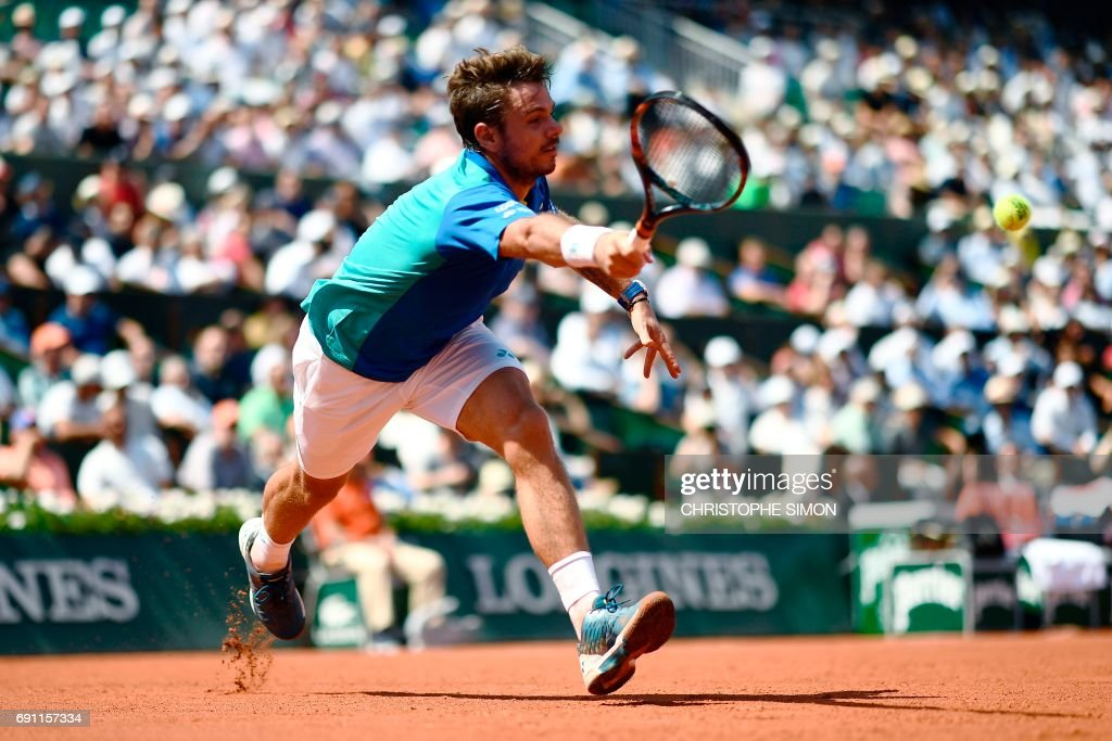TOPSHOT - Switzerland's Stanislas Wawrinka hits a return to Ukraine's Alexandr Dolgopolov during their tennis match at the Roland Garros 2017 French Open on June 1, 2017 in Paris. /
