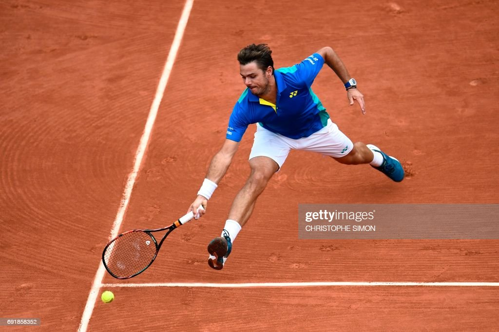 TOPSHOT - Switzerland's Stanislas Wawrinka returns the ball to Italy's Fabio Fognini during their tennis match at the Roland Garros 2017 French Open on June 3, 2017 in Paris. /