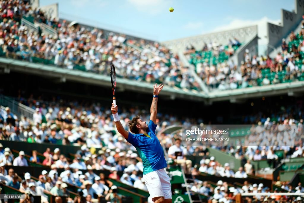 TOPSHOT - Switzerland's Stanislas Wawrinka serves to Ukraine's Alexandr Dolgopolov during their tennis match at the Roland Garros 2017 French Open on June 1, 2017 in Paris. /