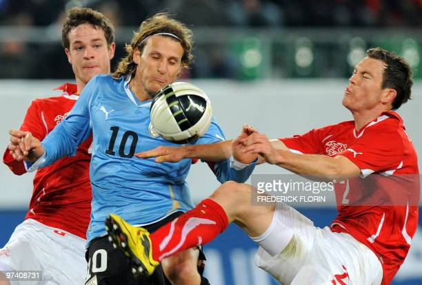 Switzerland's Stephan Lichtsteiner vies with Uruguay's Diego Forlan during the World Cup 2010 friendly football match Switzerland vs Uruguay at AFG...