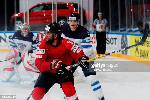 Switzerland's Thomas Rufenacht vies for the puck with Finland's Mikko Lehtonen during the IIHF Men's World Championship group B ice hockey match...