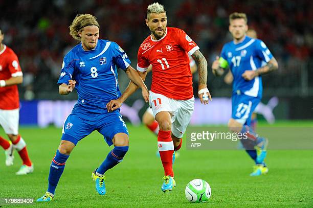Switzerland's Valon Behrami fights for the ball with Iceland's Birkir Bjarnason during a FIFA World Cup 2014 qualifying football match Switzerland vs...