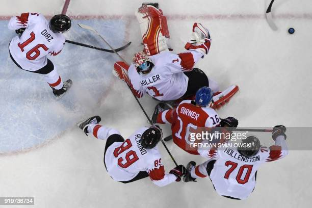 Switzerland's Vincent Praplan clears the puck away as Czech Republic's Michal Birner is surrounded by Switzerland players in the men's preliminary...