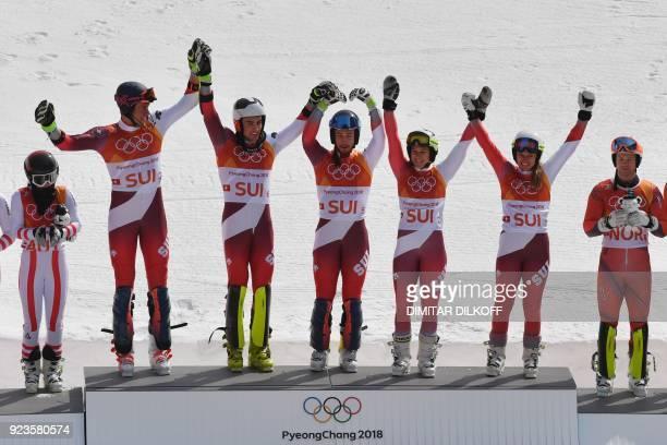 Switzerland's winners Ramon Zenhaeusern Daniel Yule Luca Aerni Wendy Holdener and Denise Feierabend pose on the podium during the victory ceremony...