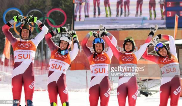 Switzerland's winners Ramon Zenhaeusern Daniel Yule Luca Aerni Wendy Holdener and Denise Feierabend make heart shapes as they pose on the podium...