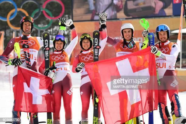 TOPSHOT Switzerland's winners Ramon Zenhaeusern Denise Feierabend Wendy Holdener Daniel Yule and Luca Aerni celebrate on the podium during the...
