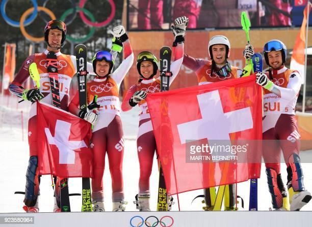 Switzerland's winners Ramon Zenhaeusern Denise Feierabend Wendy Holdener Daniel Yule and Luca Aerni celebrate on the podium during the victory...