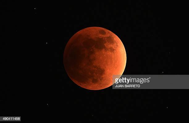 A swollen 'supermoon' is seen during the stages of a total eclipse in Caracas on September 27 2015 For the first time in decades the double spectacle...