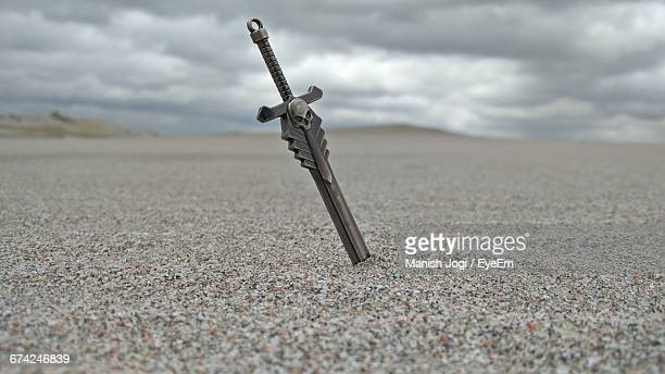 sword in sand at beach against cloudy sky - sword stock pictures, royalty-free photos & images