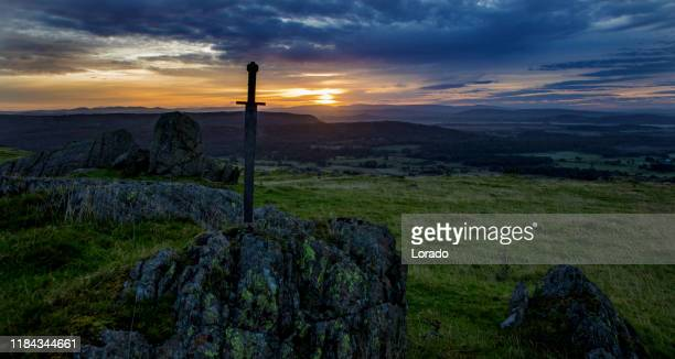 sword in the stone at dawn - sword in the stone stock photos and pictures