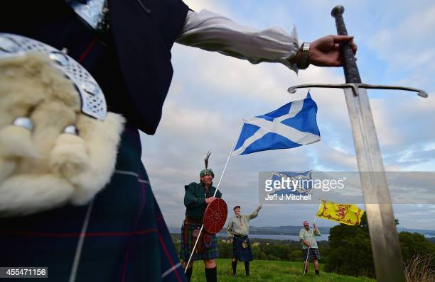 A sword is held as Duncan Thomson Brian McCutcheon John Patterson and Arthur Murdoch King of Scots Robert the Bruce Society hold the Scottish flags...