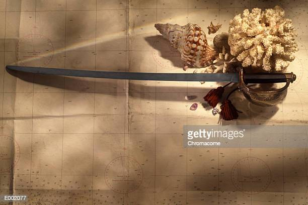 Sword, seashells, dried coral and pebbles on top of map
