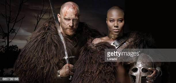 sword wielding bloody viking soldier with warrior queen - bald woman stock photos and pictures