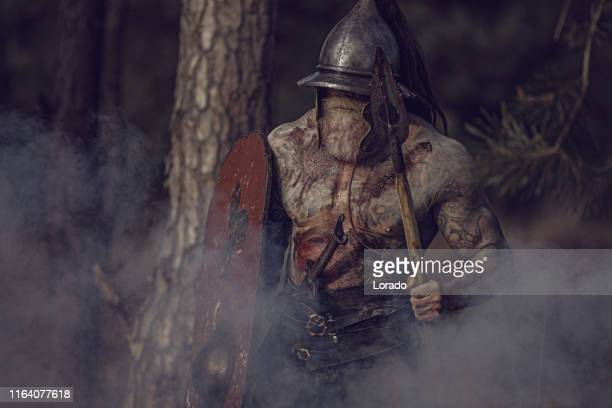sword wielding bloody viking warrior alone in a forest - barbarian stock photos and pictures
