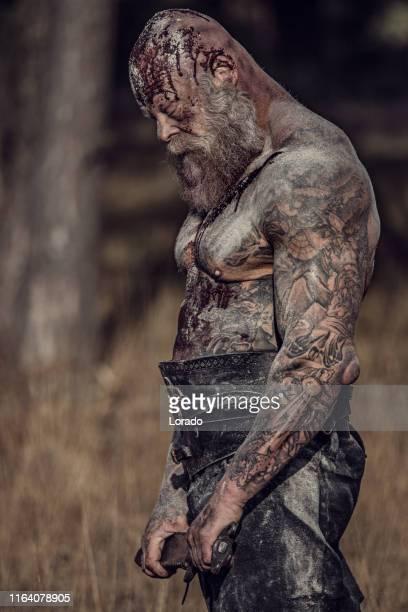 épée brandissant le guerrier viking sanglant seul dans une forêt - coiffure homme photos et images de collection