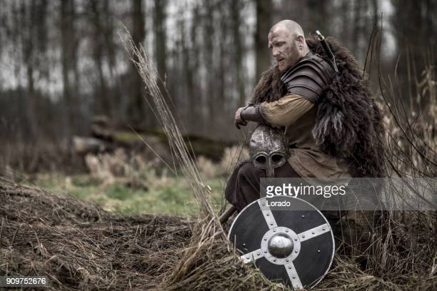 Sword wielding bloody viking warrior alone in a winter forest
