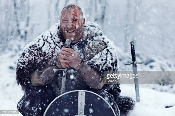 Sword wielding bloody viking warrior hidden behind his shield in a winter snowstorm