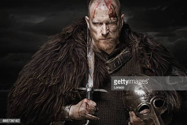 sword wielding bloody viking warrior in studio shot - barbarian stock photos and pictures