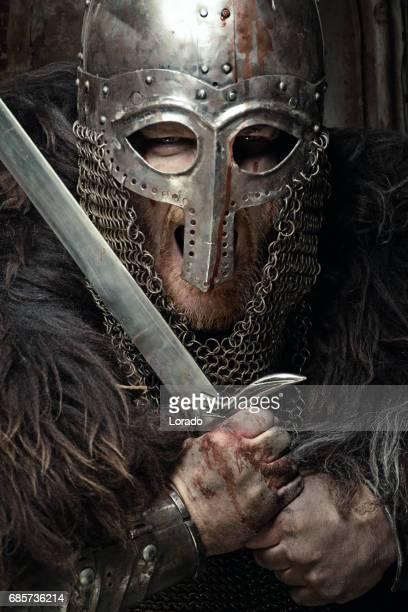 Svärd svingar blodiga viking krigare klädd i en gammal hjälm