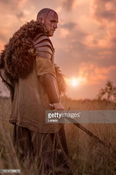espada empuñando pelirroja sangriento vikingo guerrero solo en un campo de hierba de la primavera - gladiator fotografías e imágenes de stock