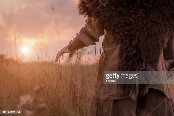 sword wielding redhead bloody viking warrior alone in a grassy springtime field - gladiator stock photos and pictures