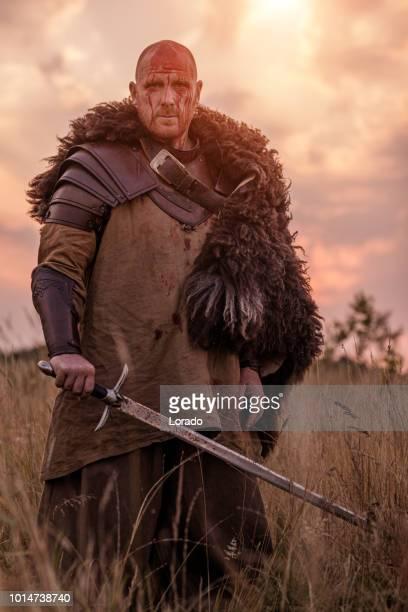 épée brandissant rousse sanglante guerrier viking seul dans un champ herbeux printemps - gladiateur photos et images de collection
