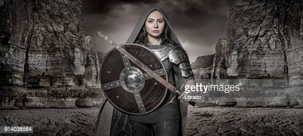 sword wielding viking warrior dark haired female in wild highland countryside - st. joan of arc stock photos and pictures