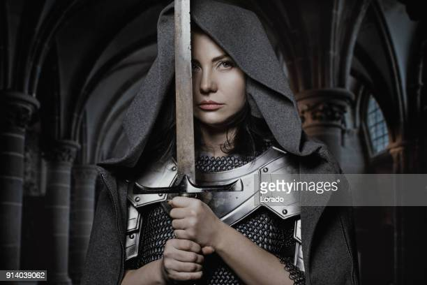 sword wielding viking warrior dark haired female in wild highland countryside - warrior person stock photos and pictures