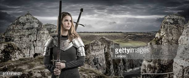 sword wielding viking warrior young blond female in wild highland countryside - st. joan of arc stock pictures, royalty-free photos & images