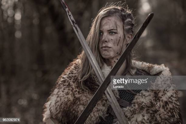sword wielding viking warrior young blond female in wild highland countryside - weaponry stock pictures, royalty-free photos & images