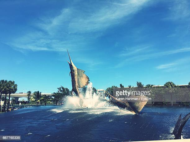 swordfish statues in fountain against sky - swordfish stock pictures, royalty-free photos & images