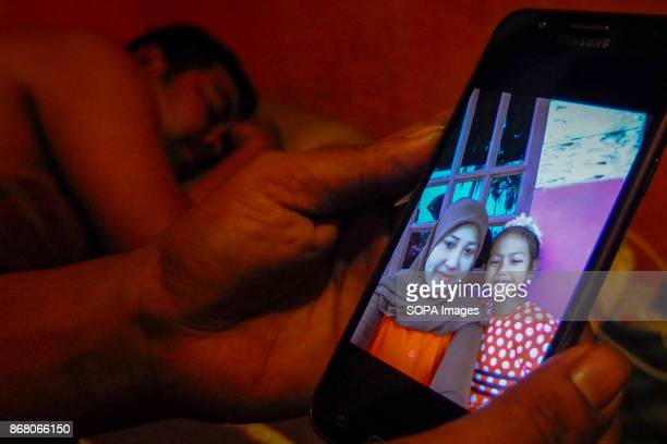 Syahrul is seen taking a rest as his friend watch family photo through the phone Malaysia count almost 17 million migrant workers in the country...