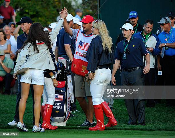 Sybi Kuchar high five caddie Lance Bennett as Lindsey Vonn and assistant captain Davis Love III follow the play of the US Team during the Day One...