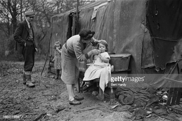 Syd Saunders and his family outside the tent where they live in the New Forest Hampshire January 1949 Their encampment is in one of six designated...
