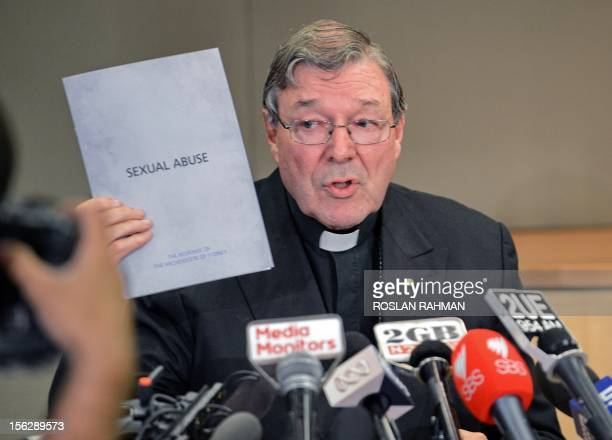 Sydney Archbishop Cardinal George Pell holds a document to the response of the archidiocese to sexual abuse during a press conference in Sydney on...