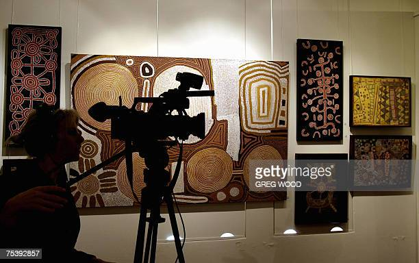 A woman films near Aboriginal artwork at Sotheby's Auction House in Sydney 12 July 2007 A painting by Clifford Possum Tjapaltjarri titled Warlugulong...
