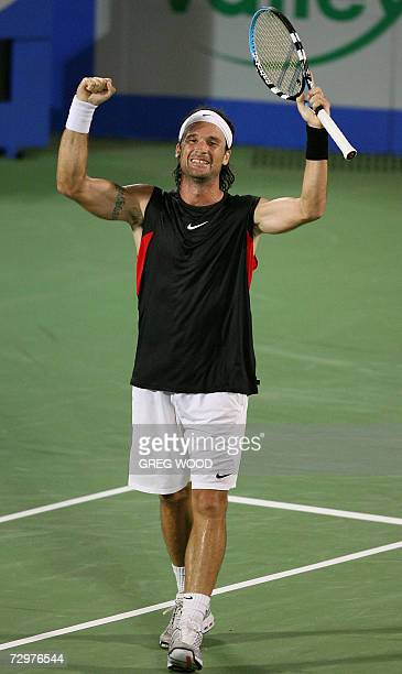 An exhausted Carlos Moya of Spain raises his arms after defeating Marcos Baghdatis of Cyprus in their quarter-final match at the Sydney International...