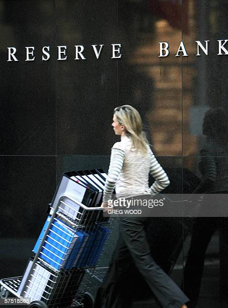 An office worker pushes files past the Reserve Bank of Australia in Sydney 03 May 2006 The RBA increased interest rates for the first time in 14...