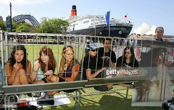 Animal rights activists sit in cages during a protest at Sydney Harbour with the luxury Queen Elizabeth ocean liner in the backgroud to mark the...