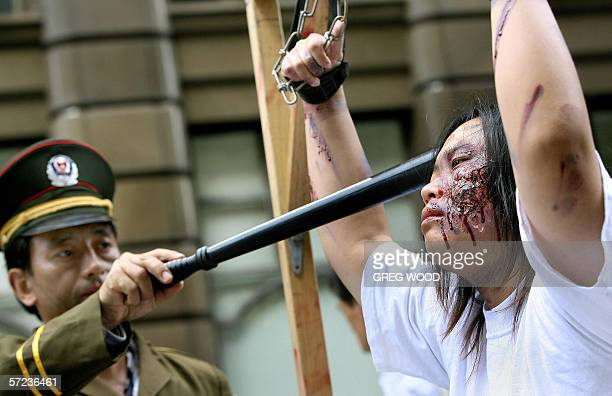 Falungong practitioners act out a torture scene as they protest in Sydney 03 April 2006 Members of the Falungong religious movement were bringing to...