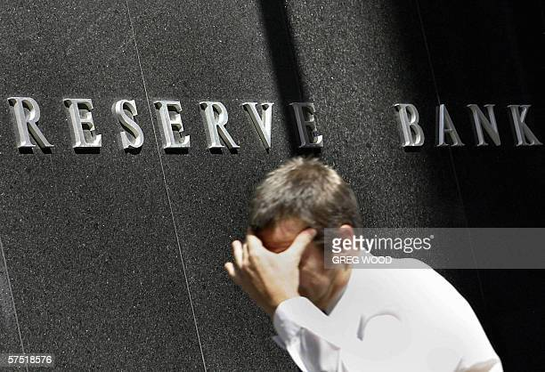Photo taken 26 October 2004 shows an office worker holding his head as he walks past the Reserve Bank of Australia in Sydney The RBA increased...