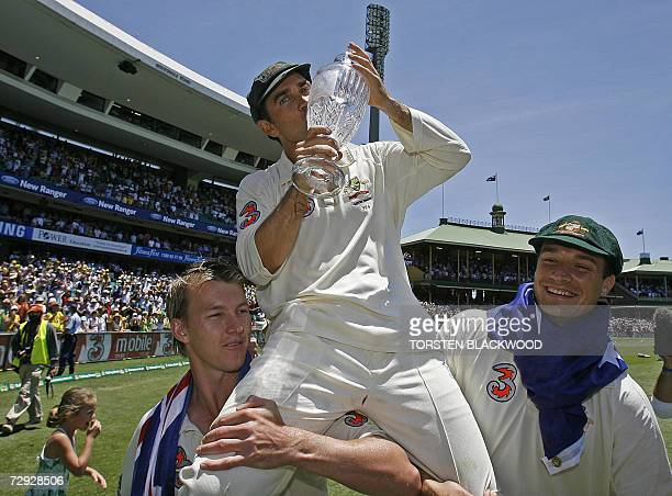 Retiring opening batsman for Australia Justin Langer kisses The Ashes trophy as he is carried by teammates Brett Lee and Stewart Clarke on a farewell...