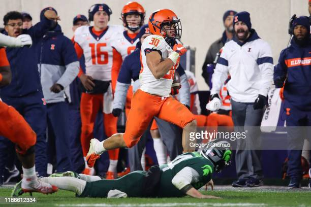 Sydney Brown of the Illinois Fighting Illini returns a interception for a fourth quarter touchdown past Brian Lewerke of the Michigan State Spartans...