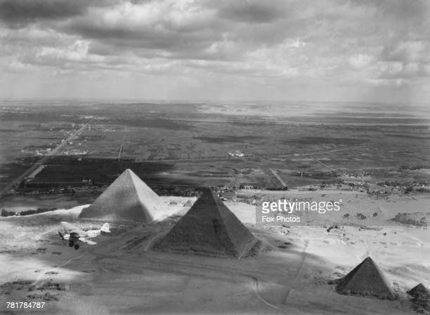 A Sydney Camm designed Hawker Hardy of 30 Squadron Royal Air Force flys over the ancient Pyramids of Giza on 1 July 1937 near Cairo Egypt