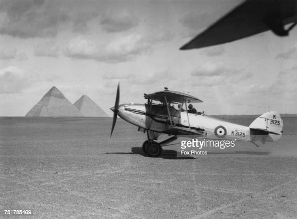A Sydney Camm designed Hawker Hardy of 30 Squadron Royal Air Force taking off near the ancient Pyramids of Giza on 1 July 1937 near Cairo Egypt